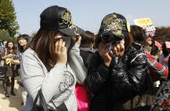 South Korean pop singer Rain's fans from Asian countries cry after Rain entered the army to serve in front of an army training center in Uijeongbu, north of of Seoul, South Korea, Tuesday, Oct. 11, 2011. (AP Photo/ Lee Jin-man)