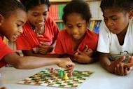 Ayta elementary students play a board game at the Camias Resettlement Elementary School in Porac, north of Manila. The hope is that, once the programme is implemented and succeeds, the government will start introducing mother-tongue instruction for the most endangered languages