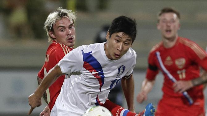 Russia's defender Andrey Yeshchenko, left, and South Korea's Keunho Lee compete for the ball during the international friendly soccer match between Russia and South Korea, in Dubai, United Arab Emirates, Tuesday, Nov. 19, 2013