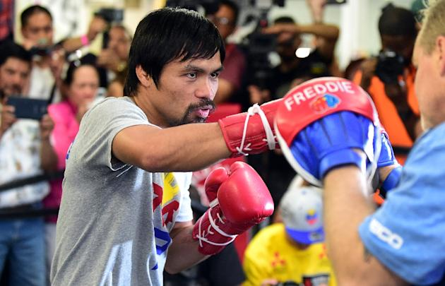 Boxer Manny Pacquiao spars with his coach Freddy Roach during a training session at the Wild Card Boxing Club in Hollywood, California on April 15, 2015