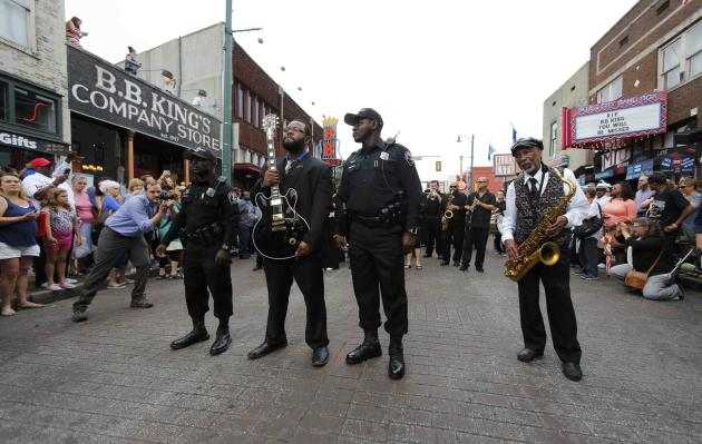 """Bland, son of Bobby """"Blue"""" Bland, pauses as he holds the iconic Gibson guitar named """"Lucille"""" belonging to the late B.B. King at the start of a procession down Beale Street in Memp"""