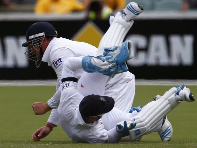 England's vice-captain Prior rolls as teammate Bell misses a catch hit by Australia's captain Clarke during the second day of the second Ashes test cricket match in Adelaide