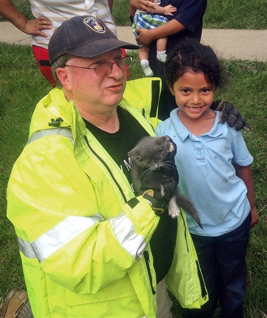 Deputy Fire Chief Glenn Usdin, left, holds the kitten that was rescued with the help of Janeysha Cruz. (Brett J. Fassnacht/Lancaster Township Fire Department via AP)