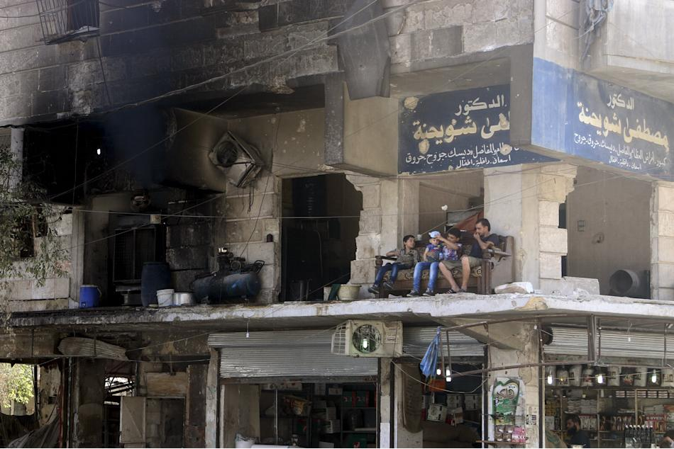 Residents sit on a couch on a balcony of a damaged building in Aleppo's al-Shaar neighboirhood, Syria