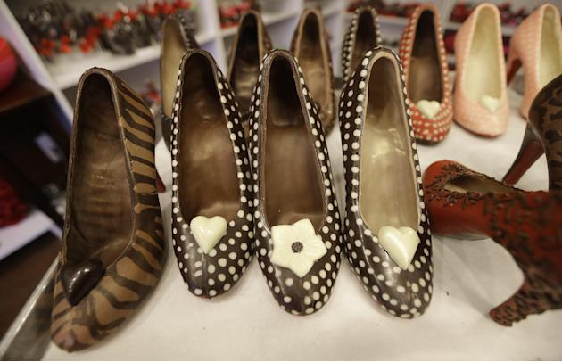 In this Feb. 7, 2013 photo, chocolate high heals made by master chocolatier Andrea Pedraza are lined up at her shop in the Oak Cliff section of Dallas. Florists and chocolate makers are working around