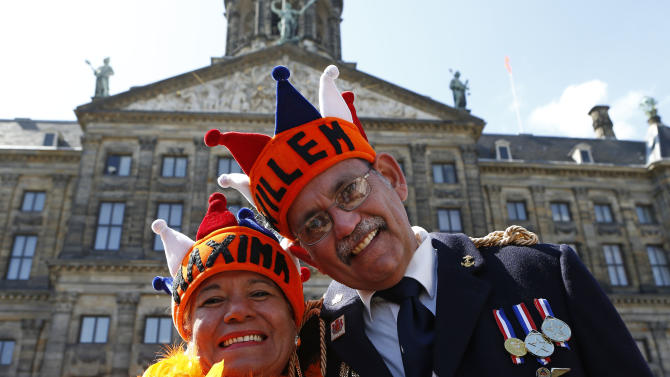 Visitors from Venezuela pose for photographers outside the Royal Palace in downtown Amsterdam, Netherlands Monday, April 29, 2013. Queen Beatrix has announced she will relinquish the crown on April 30, 2013, after 33 years of reign, leaving the monarchy to her son Crown Prince Willem-Alexander. (AP Photo/Vincent Jannink)