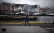 A woman walks her dog near the marina in downtown Bergen, southwestern Norway, in this March 20, 2012 file photo. REUTERS/Stoyan Nenov/Files