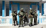Armed men stand at the entrance of the naval headquarters in Sevastopol, March 19, 2014. REUTERS/Baz Ratner