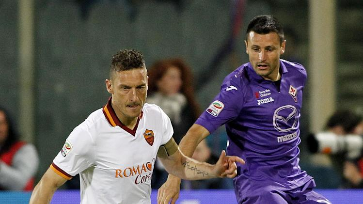 Roma's Francesco Totti, left, and Fiorentina's Manuel Pasqual go for the ball during a Serie A soccer match at the Artemio Franchi stadium in Florence, Italy,  Saturday, April 19, 2014