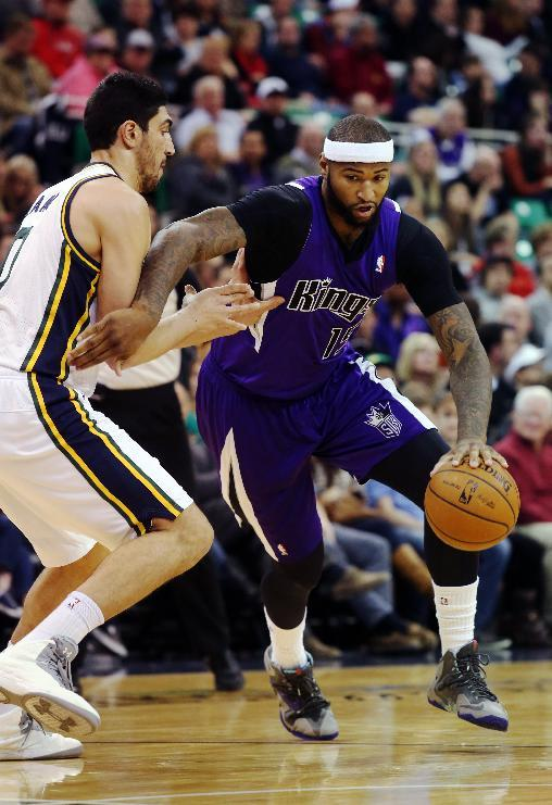 Utah Jazz's Enes Kanter, left, defends as Sacramento Kings' DeMarcus Cousins (15) drives the basket in the first half of an NBA basketball game on Saturday, Dec. 7, 2013, in Salt Lake City