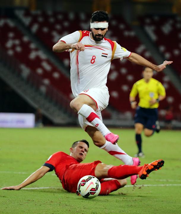 Syria's Omar Kharbin in action with Singapore's Baihakki Khaizan