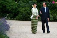 France's President Francois Hollande and Myanmar pro-democracy leader Aung San Suu Kyi walk in the garden of the Elysee presidential palace following a meeting, in Paris. Hollande told Suu Kyi Tuesday that France would do everything possible to back the country's democratic transition, as she visited Paris for the last leg of a landmark European tour