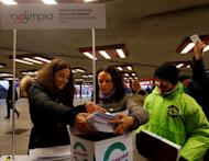 Timea Szabo(C), co-chair of opposition party Parbeszed Magyarorszagert hands over documents with signatures supporting a referendum on Budapest's 2024 Olympic bid to political movement Momentum at a stand in Budapest, Hungary, February 16, 2017.Picture taken February 16, 2017. REUTERS/Laszlo Balogh