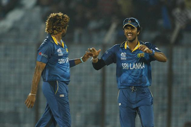 Sri Lanka's Lasith Malinga, left, celebrates with his team captain Dinesh Chandimal the wicket of Netherlands's Mudassar Bukhari during their ICC Twenty20 Cricket World Cup match against Nethe