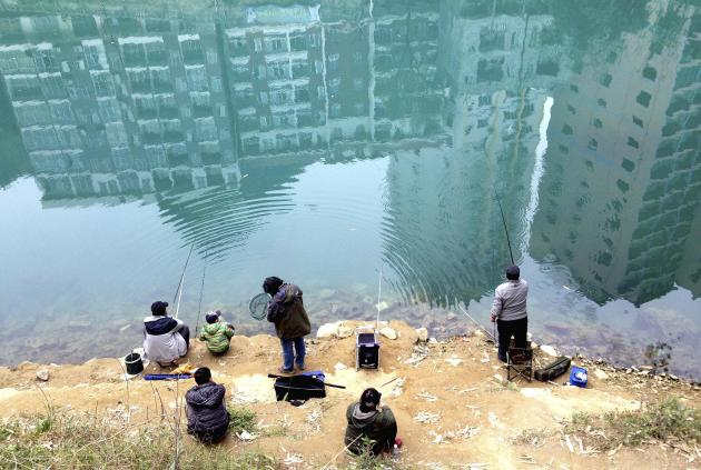 Residential buildings are reflected on the water as people fish in a river in Hechi