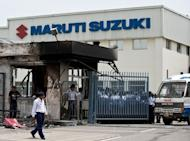 Indian private security guards stand behind the main gate of Maruti Suzuki Production Facility in Manesar, about 45 kms from New Delhi on July 19. India's biggest carmaker Maruti Suzuki reported a 23 percent plunge in quarterly profit, missing market forecasts as the company struggles to recover from deadly labour unrest