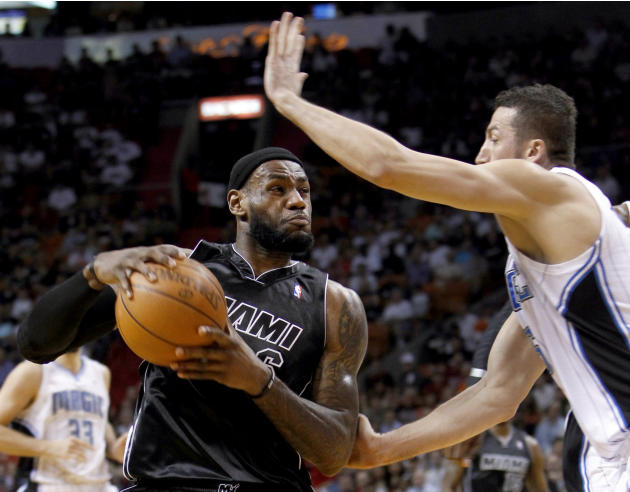 Miami Heat forward LeBron James, left, drives on Orlando Magic forward Hedo Turkoglu, right, during the first half of an NBA basketball game, Sunday, Feb. 19, 2012, in Miami. (AP Photo/Wilfredo Lee)