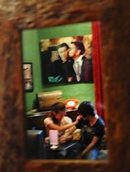This picture, taken on August 2, shows a 22-year-old lesbian, nicknamed Le Huong (L), and her 23-year-old girlfriend, nicknamed Nguyen Thi Hoa, joking around while reflected in a mirror at a bar in Hanoi. Communist Vietnam is considering legalising same-sex marriage, which would catapult it to the fore of gay rights in Asia, where traditional values dominate many societies