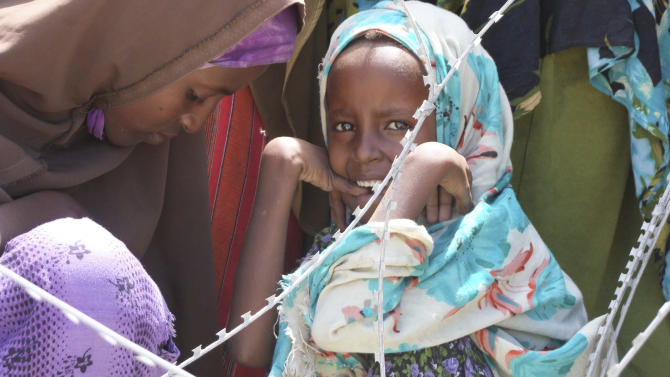 A Somali girl  from southern Somalia sit behind barbed wire in a line to receive food at a refugee camp  in Mogadishu, Somalia, Wednesday, Aug, 17, 2011. The World Food Program said Saturday that it is expanding its food distribution efforts in famine-struck Somalia, where the U.N. estimates that only 20 percent of people needing aid are getting it.(AP Photo/Farah Abdi Warsameh)