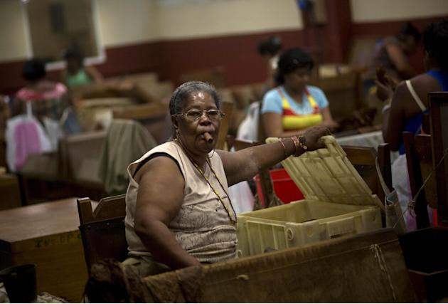 A woman smokes a cigar while she selects tobacco leaves at the H. Upmann cigar factory in Havana, Cuba, Thursday, Feb. 26, 2015. Cuban cigar makers are licking their chops over new U.S. rules that let