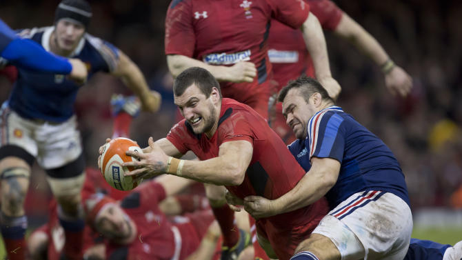 Wales' captain Sam Warburton, centre, breaks past France's Nicolas Mas as he scores a try during their Six Nations rugby union international match at the Millennium Stadium, Cardiff, Wales, Friday, Feb. 21, 2014. (AP Photo/Jon Super)