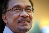 File- This Nov. 7, 2014, file photo shows Malaysian opposition leader Anwar Ibrahim, smiling as he waits for the final hearing of his sodomy conviction in Putrajaya, Malaysia. Ibrahim tells The Associated Press he's confident of acquittal in his sodomy trial, so long as the Southeast Asian nation's top court demonstrates independence. Anwar spoke Friday, Nov. 21, 2014, as he rounded off a speaking tour at U.S. universities. (AP Photo/Vincent Thian, File)