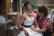 Designer Julie Hass (R) of Stockton, Illinois puts the final touches on her creation worn by Jewel Howard of Iowa named 'Jubilee' during the 10th annual toilet paper wedding dress contest in Midtown, New York June 12, 2014. REUTERS/Adrees Latif