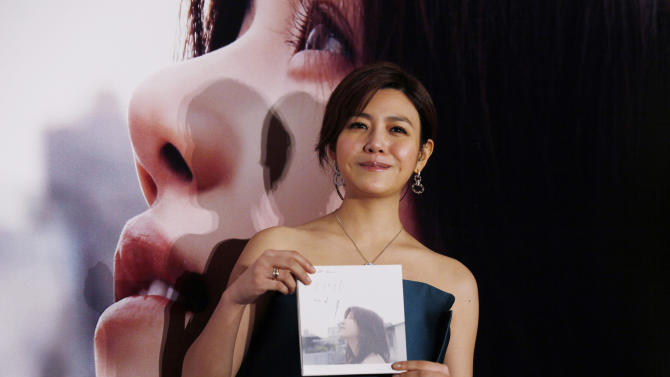 "FILE - In this Wednesday, May 8, 2013 file photo, Taiwanese singer-actress Michelle Chen poses with her new song album ""Me Myself and I"" during a promotional event for the album in Hong Kong. Fans know her as the sweet schoolgirl in the 2011 blockbuster ""You Are the Apple of My Eye."" Now, they can take a closer look at Michelle Chen through her first love: music. The 29-year-old actress said she poured her heart and soul into her first studio album, ""Me Myself and I."" (AP Photo/Kin Cheung, File)"