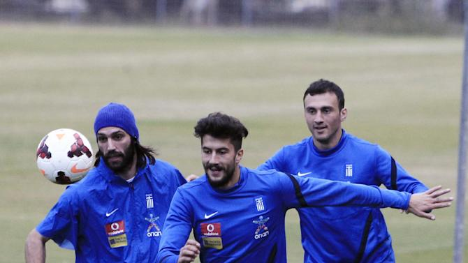 Greece's Panagiotis Kone, center, Giorgos Samaras, left, and Vassilis Torosidis run for the ball during a training session in Athens, Thursday, Nov. 14, 2013. The Greek national soccer team will face Romania for a World Cup qualifying playoff on Friday