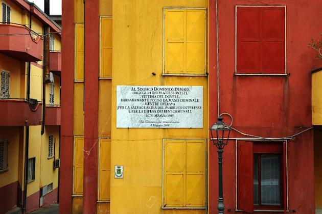 """A plaque on the city hall's facade pays homage to a former mayor, Domenico Dimaio: """"the pride of the honest residents of Plati, victim of his duty, assassinated in barbaric fashion at the han"""