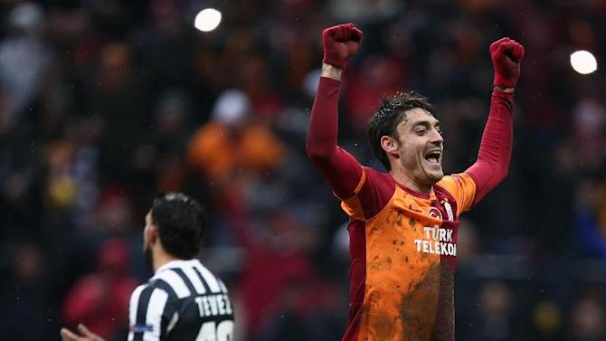 Galatasaray's Albert Riera celebrates after their Champions League soccer match victory over Juventus at the TT Arena Stadium in Istanbul, Turkey, Wednesday, Dec. 11, 2013. The match was halted Tuesday in the 31st minute with the score at 0-0 as hail and snow began to fall heavily in Istanbul, but resumed Wednesday. Carlos Tevez of Juventus is at the rear.(AP Photo)