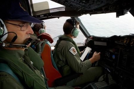 Co-Pilot, Flying Officer Marc Smith (R) and crewmen aboard a Royal Australian Air Force (RAAF) AP-3C Orion aircraft, search for the missing Malaysian Airlines Flight MH370 over the southern Indian Ocean March 24, 2014. REUTERS/Richard Wainwright/Pool