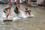 Children use plywood to surf in a flooded street in the town of Navotas in suburban Manila on August 2, 2012. A Philippine gold mining firm said Friday waste had leaked from one of its mines due to heavy rains, forcing the government to shut down production