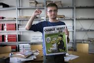 French satirical weekly Charlie Hebdo's publisher, known only as Charb, clenches his fist as he presents Wednesday's issue of the magazine to journalists in Paris. The magazine contains nude cartoons of the Prophet Mohammed