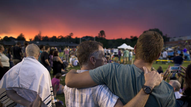 The sun sets as mourners gather for a candlelight vigil in Prescott, Ariz. Tuesday, July 2, 2013 to honor the 19 Granite Mountain Hotshot firefighters who were killed by an out-of-control blaze near Yarnell, Ariz. on Sunday. (AP Photo/Julie Jacobson)
