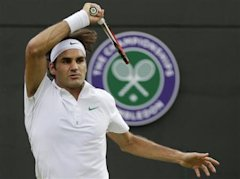 Roger Federer of Switzerland plays a return to Albert Ramos of Spain during a first round men's singles match at the All England Lawn Tennis Champions