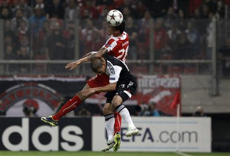 Olympiakos Piraeus' Holebas jumps for the ball next to Benfica's Pereira during their Champions League soccer match in Piraeus near Athens