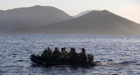 wMembers of Philippine marines are transported on rubber boat from a patrol ship, after mission at disputed Second Thomas Shoal, as they return to naval forces camp in Palawan