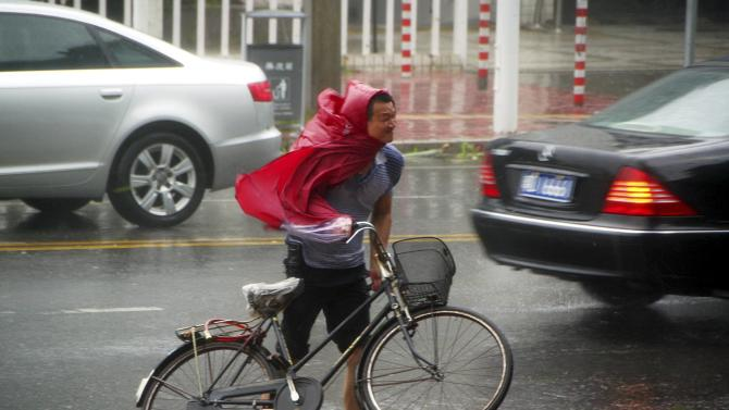 A man pushes his bicycle against the wind as Typhoon Usagi approaches Shantou, Guangdong province