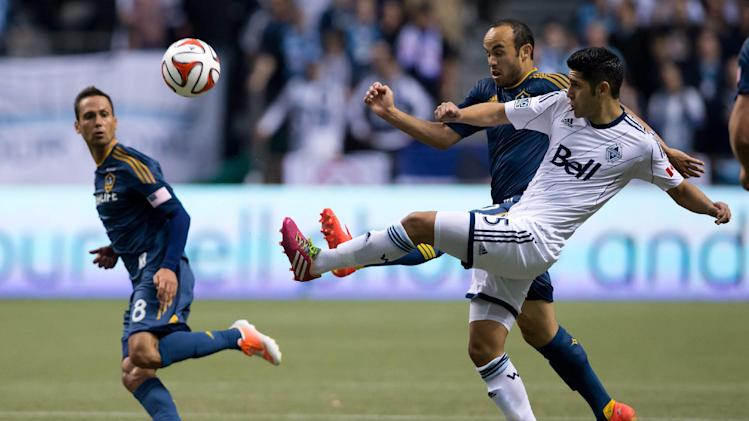 Vancouver Whitecaps' Matias Laba, right, of Argentina, kicks the ball past Los Angeles Galaxy's Landon Donovan, back right, as Marcelo Sarvas, left, of Brazil, watches during the second half of an MLS soccer game on Saturday, April 19, 2014, in Vancouver, British Columbia