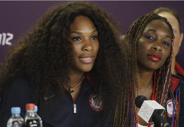 American tennis player Serena Williams, left, responds to questions as Venus Williams looks on during a news conference before the start of the Olympic Games Tuesday, July 24, 2012, in London. (AP Pho