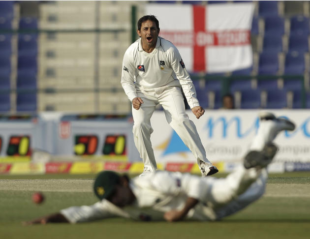 Pakistan's Saeed Ajmal reacts as his teammate Mohammad Hafeez tries to catch the ball during the second day of the second cricket test match of a three match series between England and Pakistan at the