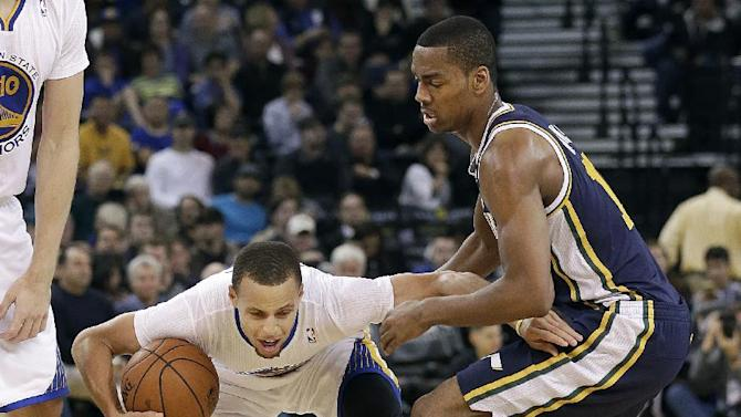 Golden State Warriors shooting guard Stephen Curry, left, tries to dribble past Utah Jazz point guard Alec Burks during the second quarter of an NBA basketball game in Oakland, Calif., Saturday, Nov. 16, 2013
