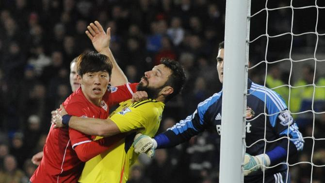 Cardiff City's Kim challenges Sunderland's Dossena during their English Premier League soccer match in Cardiff