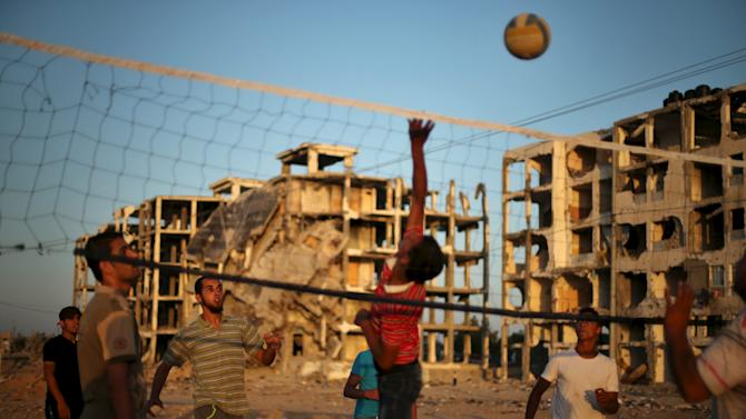 Palestinians play volleyball near residential buildings, that witnesses said were heavily damaged by Israeli shelling during a 50-day war last summer, in Beit Lahiya town