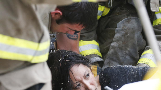 A woman is pulled out from under tornado debris at the Plaza Towers School in Moore, Okla., Monday, May 20, 2013. A tornado as much as half a mile (.8 kilometers) wide with winds up to 200 mph (320 kph) roared through the Oklahoma City suburbs Monday, flattening entire neighborhoods, setting buildings on fire and landing a direct blow on an elementary school.(AP Photo Sue Ogrocki)