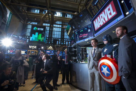 Actors Chris Evans and Sebastian Stan pose for photographs with a man dressed as Captain America on the floor of the New York Stock Exchange