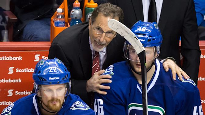 Vancouver Canucks coach John Tortorella, center, talks to Nicklas Jensen, right, of Denmark, after the team gave up a goal to the Anaheim Ducks during his shift, as Daniel Sedin, left, of Sweden, listens during the second period of an NHL hockey game Saturday, March 29, 2014, in Vancouver, British Columbia