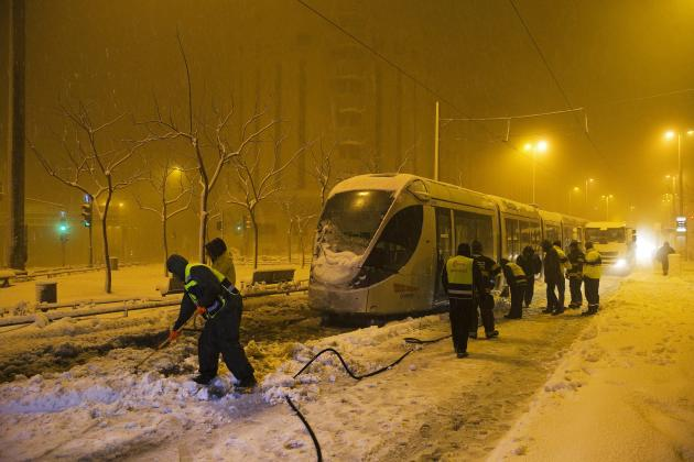 Municipality workers clear snow from the tracks of the light rail tram early morning in Jerusalem