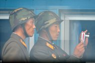 North Korean soldiers are seen through a window from the U.N. Command Military Armistice Commission meeting room at the truce village of Panmunjom in the demilitarized zone separating the two Koreas on Wednesday July 27, 2011. U.N. and U.S. military officers visited Panmunjom to mark the 58th anniversary of the cease-fire for the 1950-53 Korean War. (AP Photo/Kim Jae-hwan, Pool)